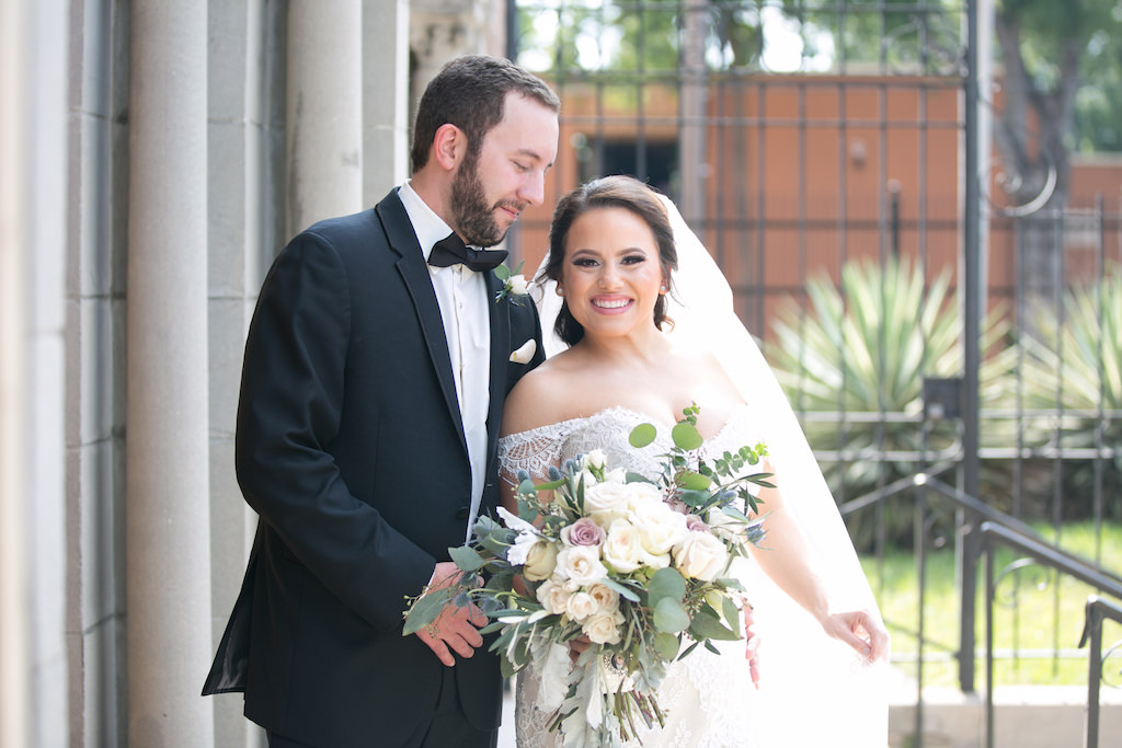 Outdoor Church Steps Wedding Portrait, Bride in Off The Shoulder Lace Augusta Jones Dress with Cream, Blush, Mauve Rose and Thistle Bouquet with Greenery, Groom in Black Tux with Bow Tie and Pink Pocket Square   Tampa Bay Wedding Photographer Carrie Wildes Photography