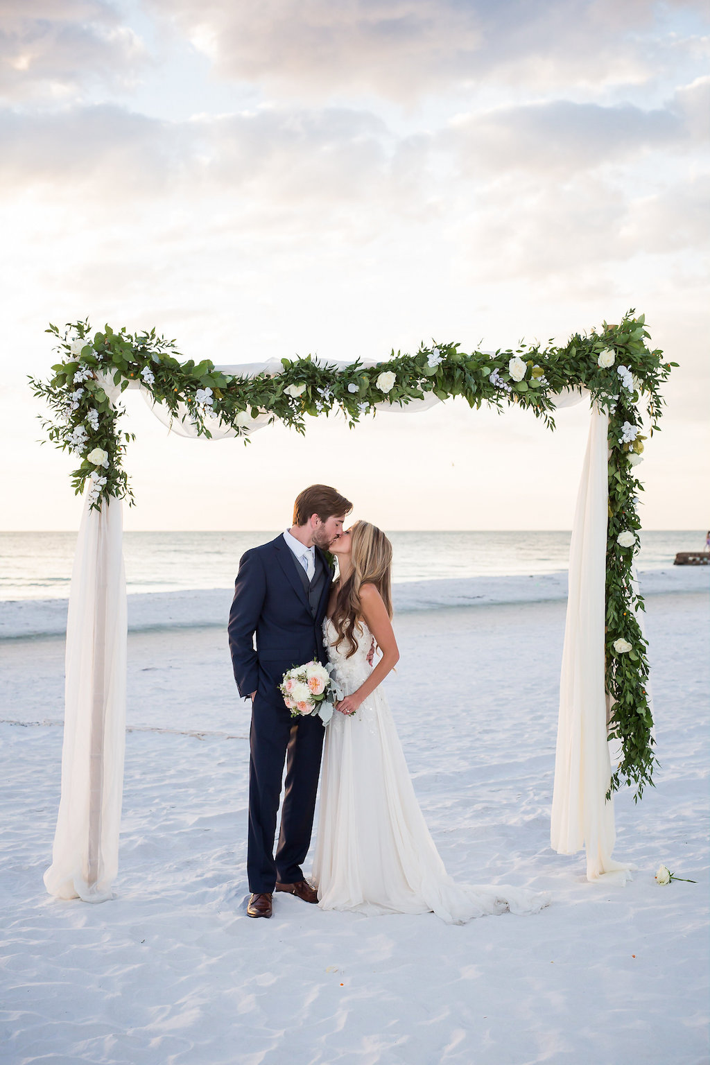 Bride and Groom Kissing Under White Draped Arch Accented with Greenery and White Flowers   Siesta Key Beach Wedding   Sarasota Wedding Photographer Cat Pennenga Photography