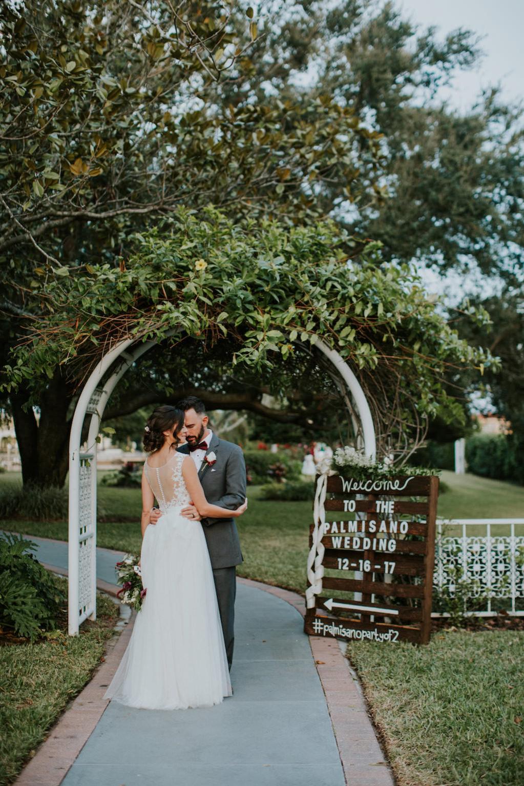 Outdoor Bride and Groom Wedding Portrait. White Arch and Rustic Wooden Crate Sign | Tampa Bay Wedding Venue Davis Islands Garden Club