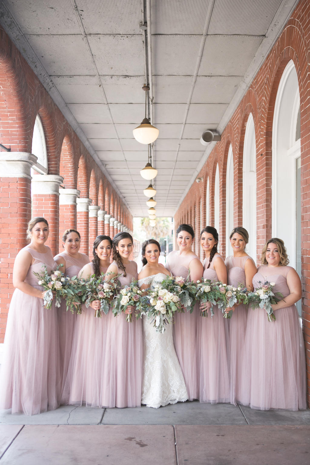 Outdoor Architectural Bridal Party Portrait, Bride in Off The Shoulder Lace Mermaid Augusta Jones Dress, Bridesmaids in Matching Strapless Layered Mauve Pink Jenny Yoo Dresses, with Blush Rose and Floral and Greenery Bouquet   Tampa Bay Wedding Photographer Carrie Wildes Photography   Dress Shop Bella Bridesmaids