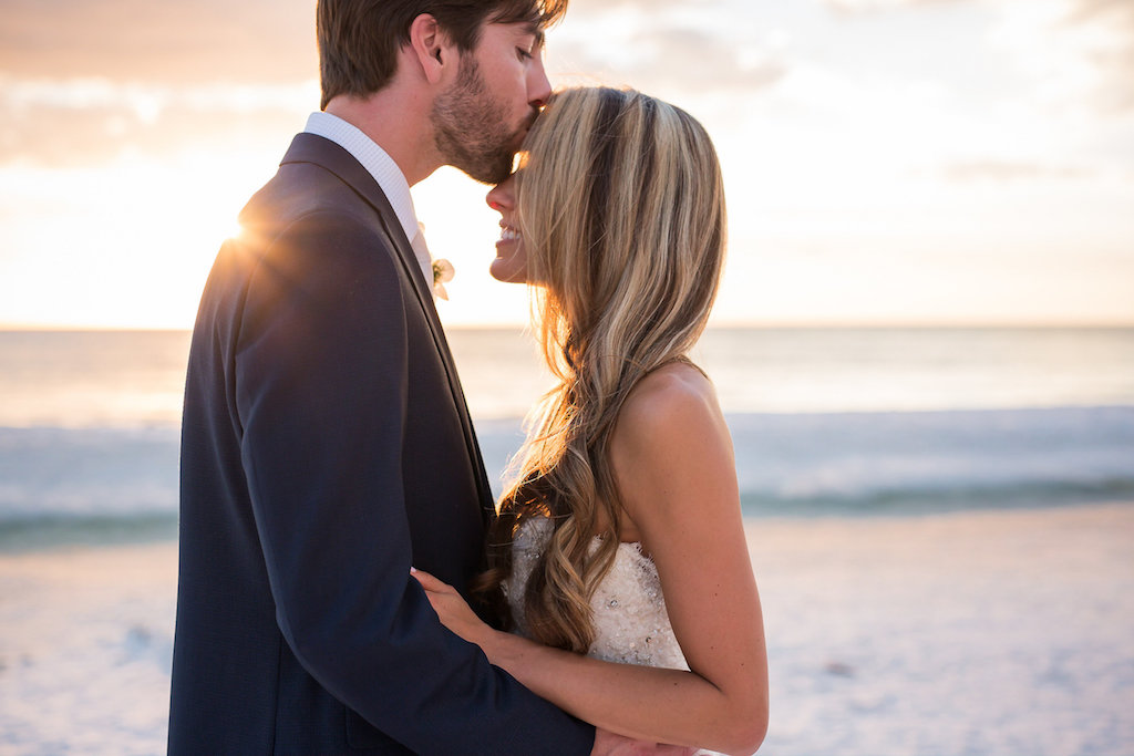 Groom Kissing Bride on Forehead During Sunset on Siesta Key Beach Wedding Portrait with Hair Wavy and Down   Sarasota Wedding Photographer Cat Pennenga Photography