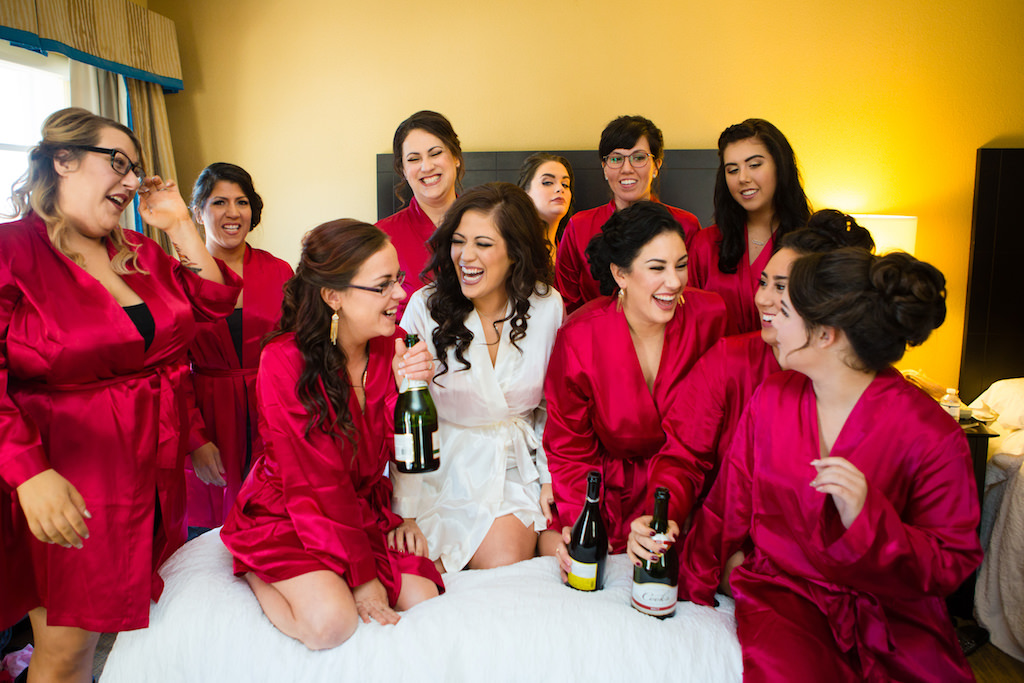 Bride And Bridesmaids Getting Ready Wedding Portrait In Matching Red Robes Bride Wearing White Tampa Bay Hair And Makeup Artist Femme Akoi Marry Me Tampa Bay Local Real Wedding