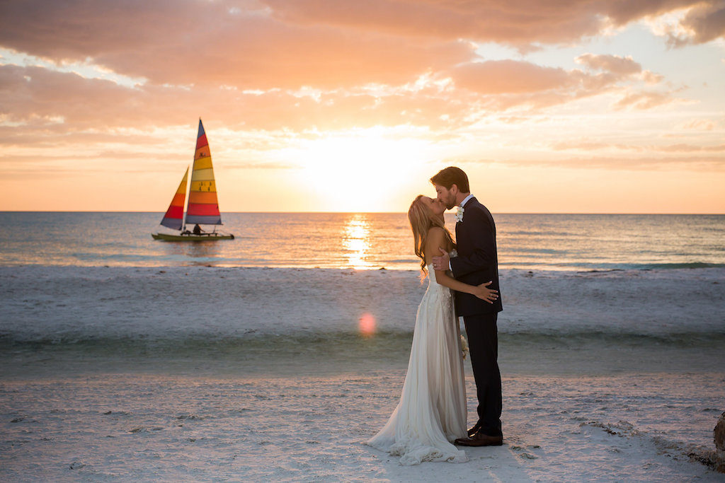 Florida Bride and Groom Kissing During Sunset on Siesta Key Beach with Sailboat in Background Wedding Portrait   Photographer: Cat Pennenga Photography