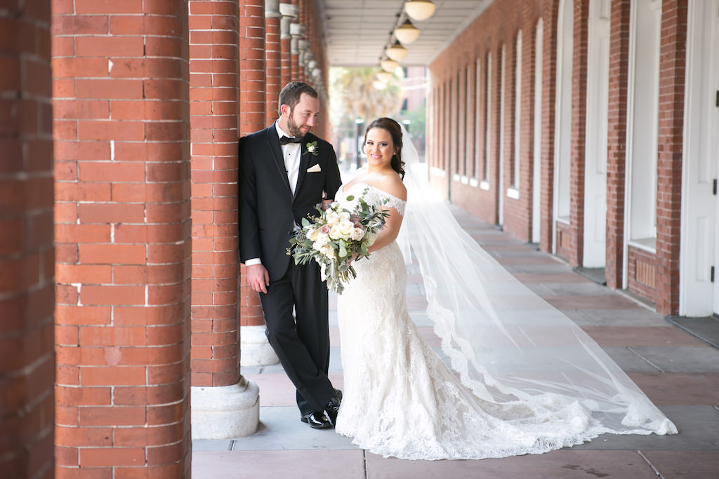 Outdoor Wedding Portrait, Bride in Off The Shoulder Lace Augusta Jones Dress with Long Lace Edged Veil, with Cream, Blush, Mauve Rose and Thistle Bouquet with Greenery, Groom in Black Tux with Bow Tie and Pink Pocket Square   Tampa Bay Wedding Photographer Carrie Wildes Photography
