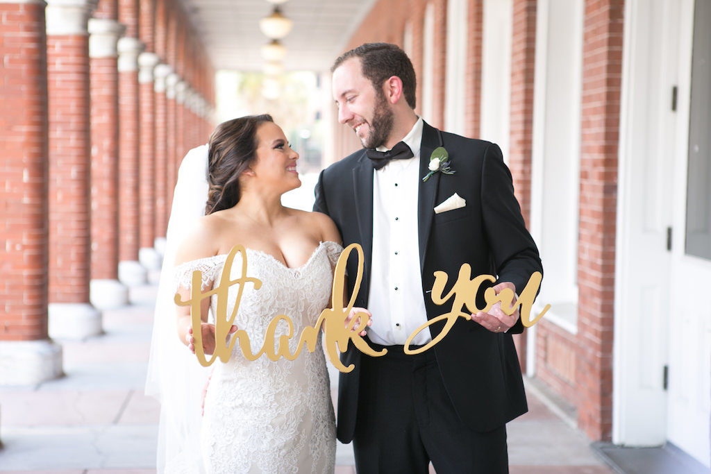 Outdoor Wedding Portrait with Stylish Gold Oversized Letter Thank You Sign, Bride in Off The Shoulder Lace Augusta Jones Dress, Groom in Black Tuxedo with Bow Tie, Blush Pink Pocket Square and Rose Boutonniere with Greenery | Tampa Bay Wedding Photographer Carrie Wildes Photography
