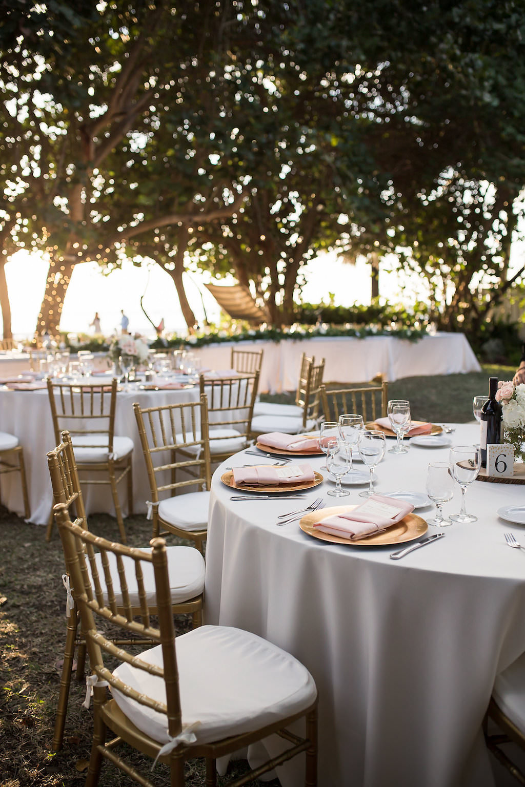 Round Reception Tables with Grey Linens Gold Chiavari Chairs Gold Chargers with Pink Napkins and Menus