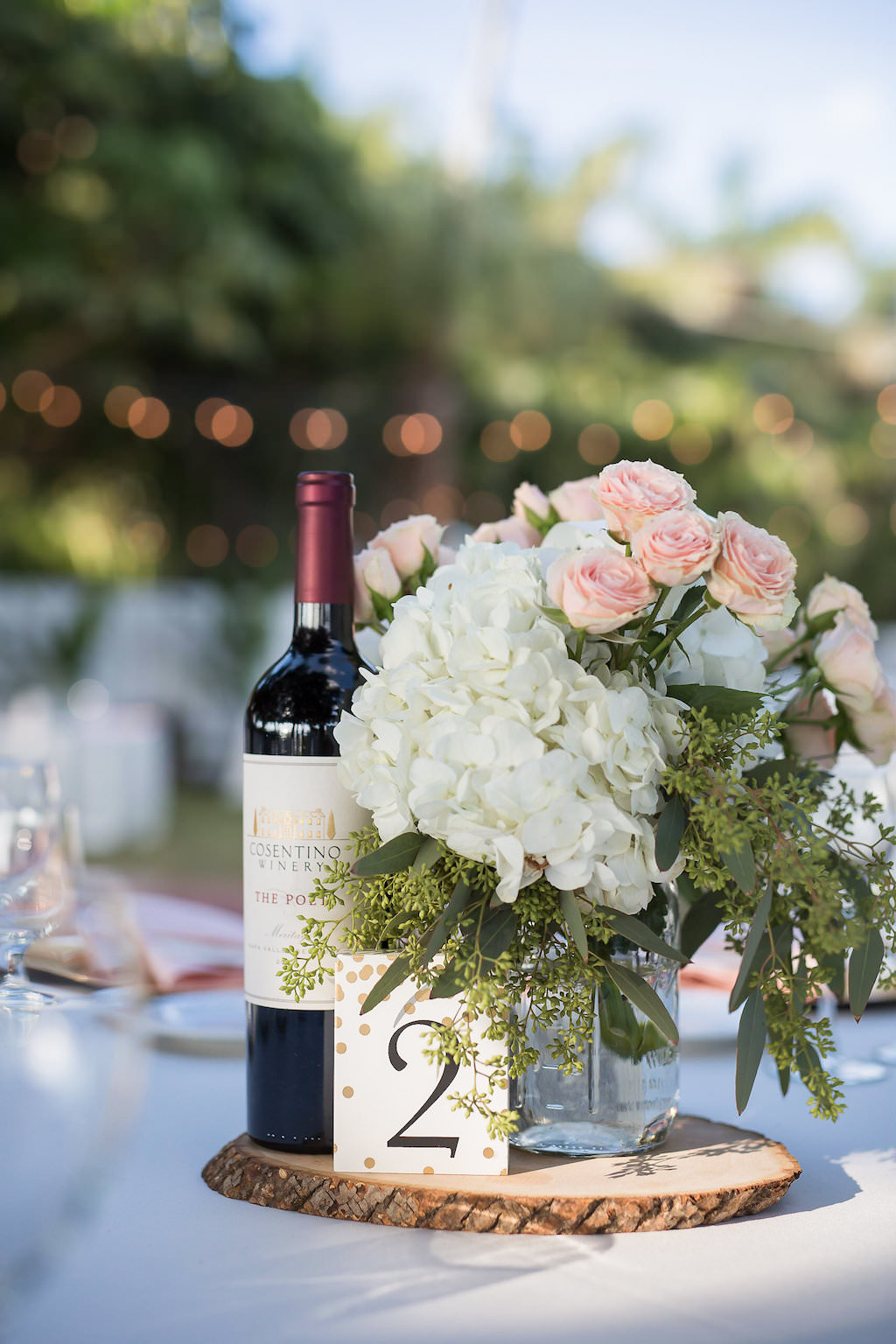 Wedding Reception Centerpiece of Wine Bottle Polka Dotted Number Sign Hydrangeas, Pink Roses and Greenery in Mason Jar on Top of Rustic Wood Slab on Grey Linen