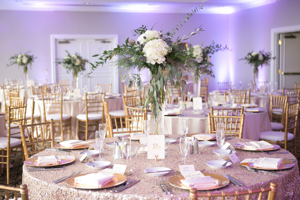Romantic Wedding Reception with Tall White Floral and Natural Greenery Centerpiece in Glass Cylinder Vase, Round Tables with Gold Chiavari Chairs and Rose Gold Sequin Linens, Gold Printed on White Card Table Number, and Gold Chargers   Tampa Wedding Venue Centre Club