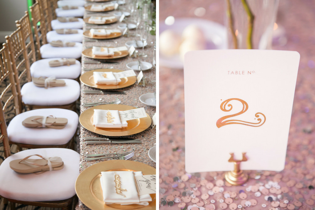 Romantic Wedding Reception Long Feasting Table with Flip Flop Favors, Gold Letter Place Cards, Chiavari Chairs, Rose Gold Sequin Linens, Gold Chargers, and Stylish Printed White Card Table Number