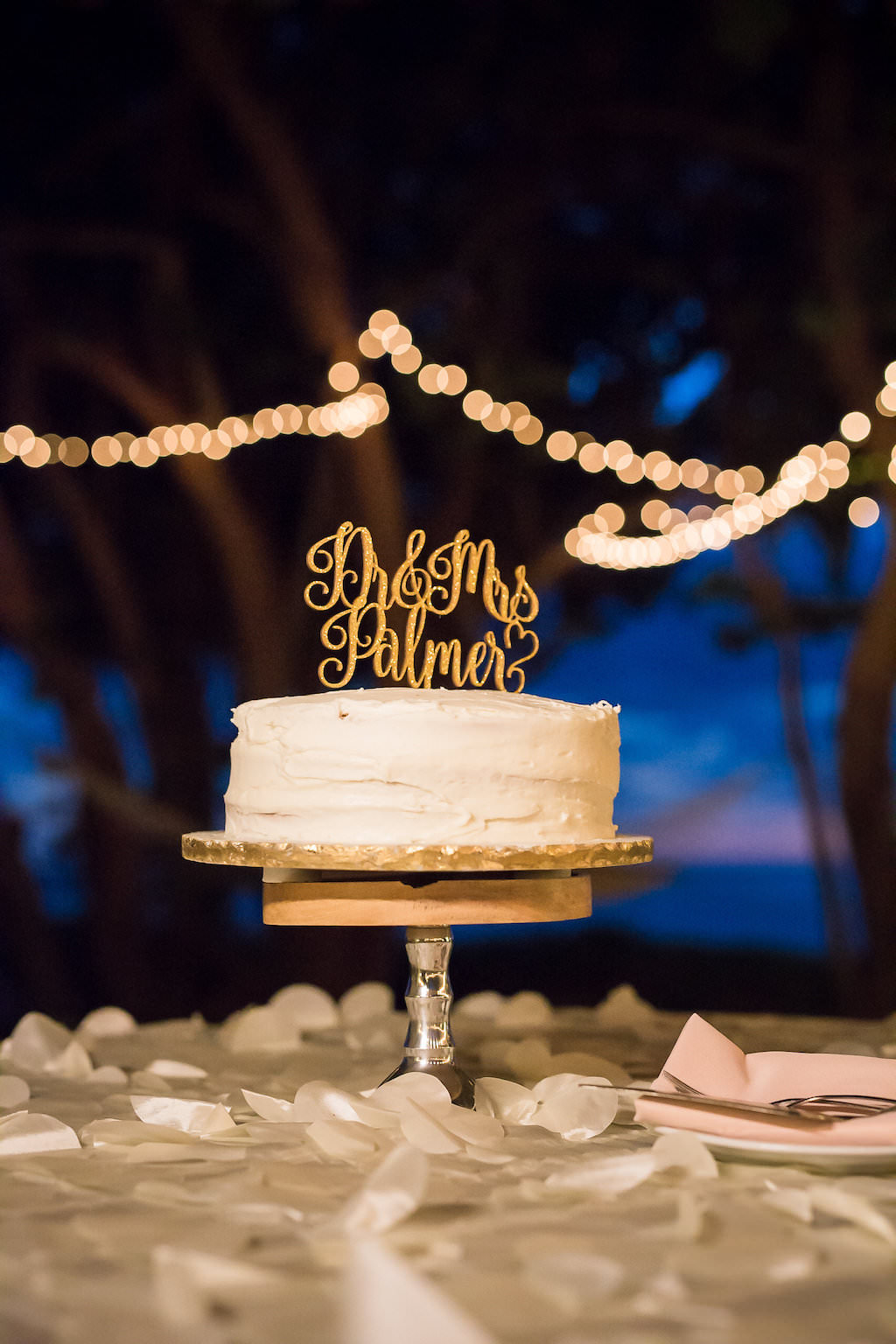 White One Tier Wedding Cake with Gold Cake Topper on Grey Linen