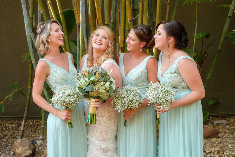 Outdoor Bridal Party Wedding Portrait, Bride in Fit and Flare Lace and Ruffle Skirt Wedding Dress with Tank Top Straps and Plunging V-Neckline, Bridesmaids in Matching Lace Bodice Bridesmaids Dresses with Greenery and White Floral Bouquet | St. Pete Photographer Marc Edwards Photography | Downtown St. Pete Wedding Venue NOVA 535
