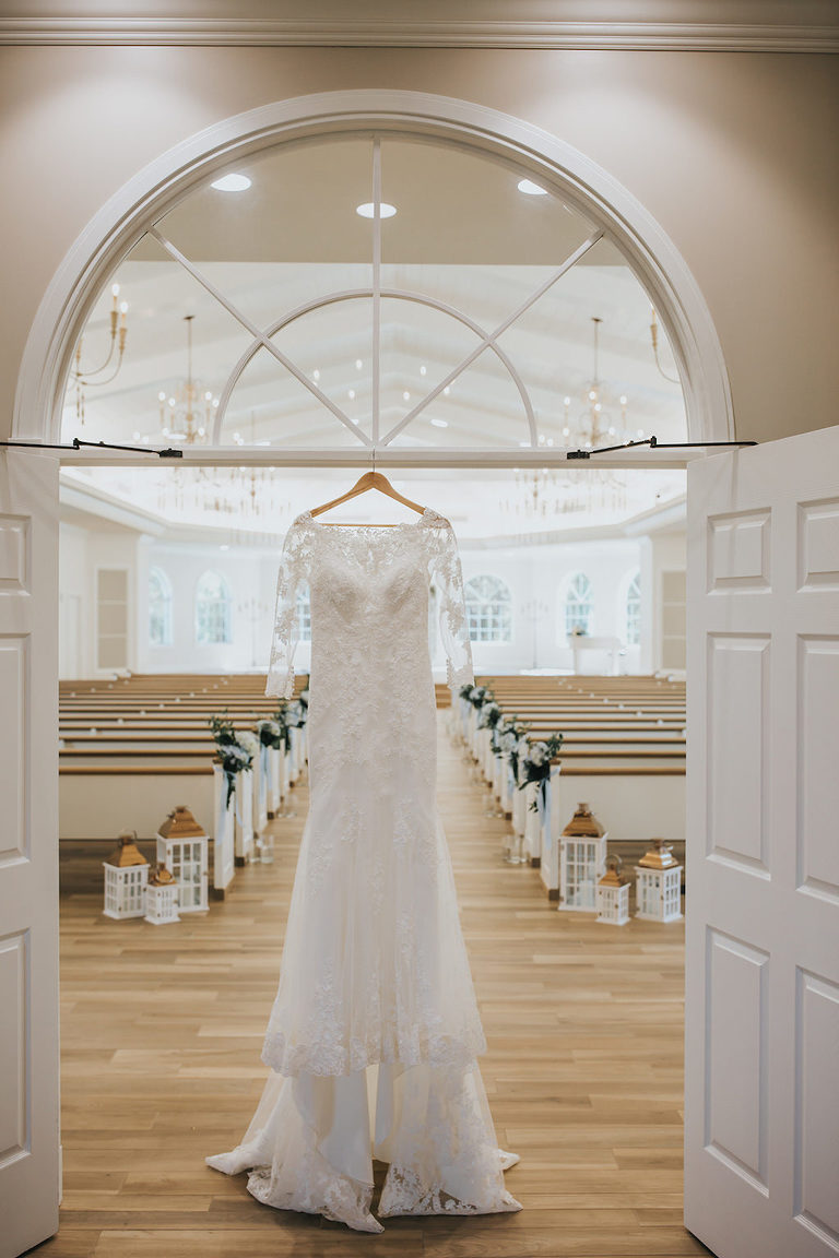 White Stella York Lace Wedding Dress with Long Sleeves Hanging on Wooden Hanger in Venue | Safety Harbor Wedding Ceremony Venue Harborside Chapel