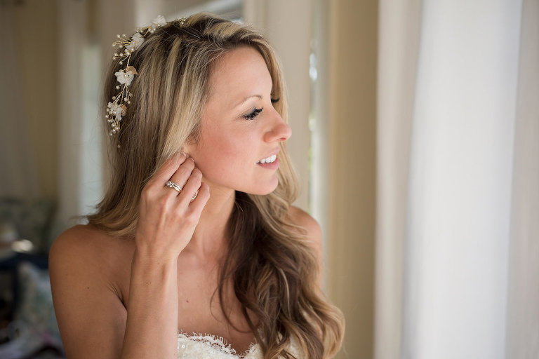 Bridal Portrait of Bride Putting on Earring with Hair Down and Wavy Wearing Flower Headpiece