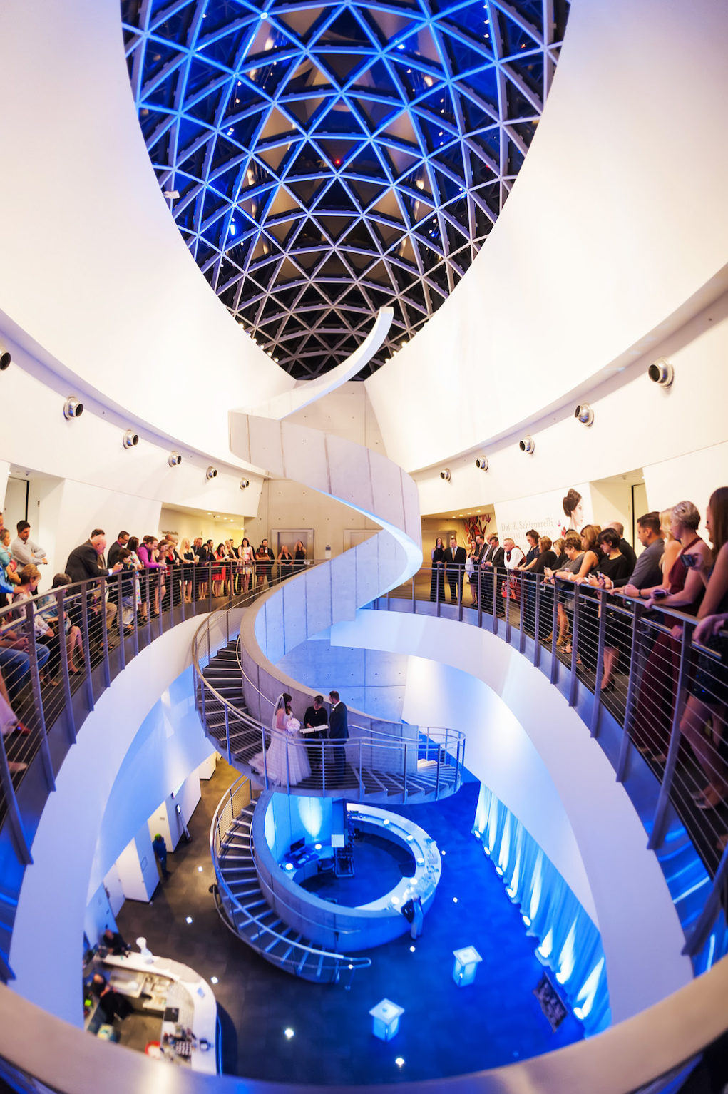 Salvador Dali Museum Ceremony Spiral White Staircase with Blue Uplighting and Bride and Groom Exchanging Vows with Guests Overlooking Balcony