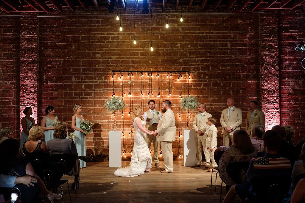 Bride and Groom Wedding Ceremony Portrait, Exposed Brick and Industrial String Lights, White Pedestals with Glass Cylinders and Baby's Breathe | Modern Industrial Wedding Reception Decor Inspiration | Downtown St. Petersburg Wedding Venue NOVA 535 | St. Pete Photographer Marc Edwards Photography