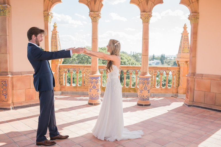 Bride and Groom Ringling Museum's Ca' d'Zan First Look Photo Groom Wearing Blue Suit and Bride in Floor Length White Wedding Dress and Hair Down | Sarasota Wedding Photographer Cat Pennenga Photography