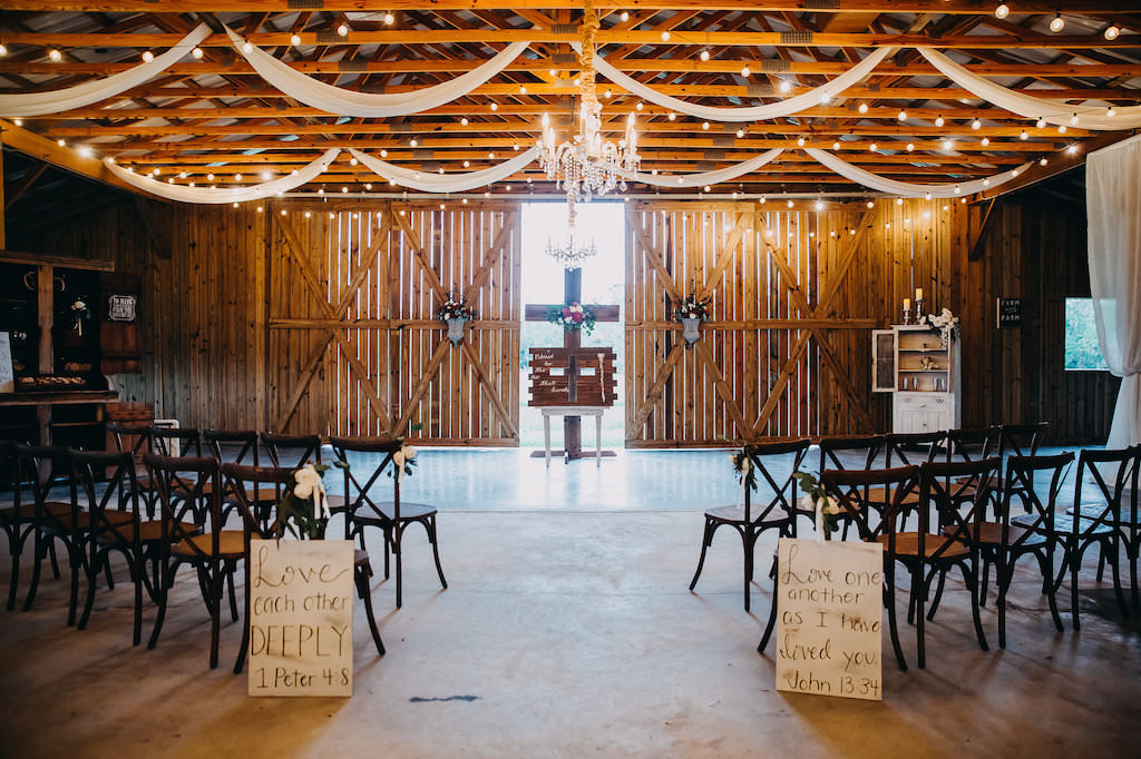 Elegant Romantic Barn Wedding Ceremony Decor With String Market Lights Ceiling Draping And Chandelier Wooden French Country Chairs Wooden Cross With Red White And Greenery Bouquet And Wedding Aisle Signage Tampa