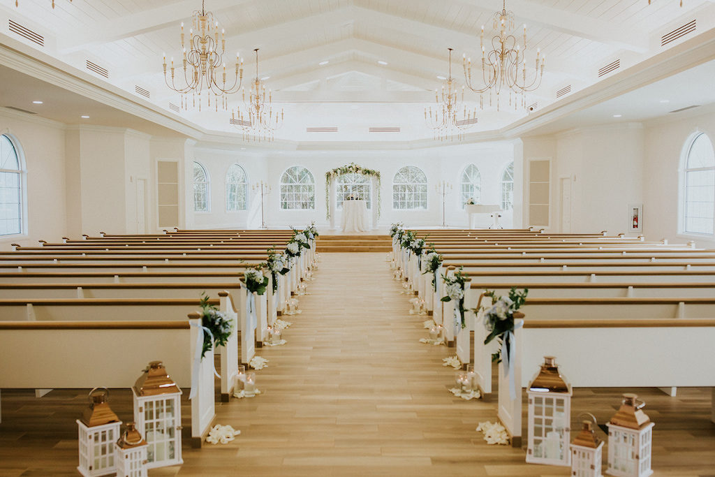 White Ceremony Decor with Lantern Aisle Decor and Greenery | Safety Harbor Wedding Ceremony Venue Harborside Chapel