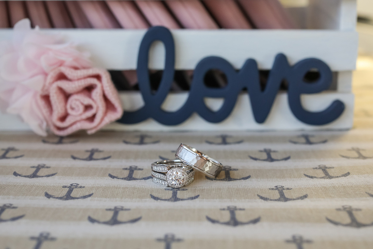 Double Band Diamond Wedding Ring, Round Engagement Ring with Diamond Halo, and Silver Men's Ring on Nautical Linen and Blue Wooden Love Sign | Tampa Bay Wedding Photographer Lifelong Photography Studio