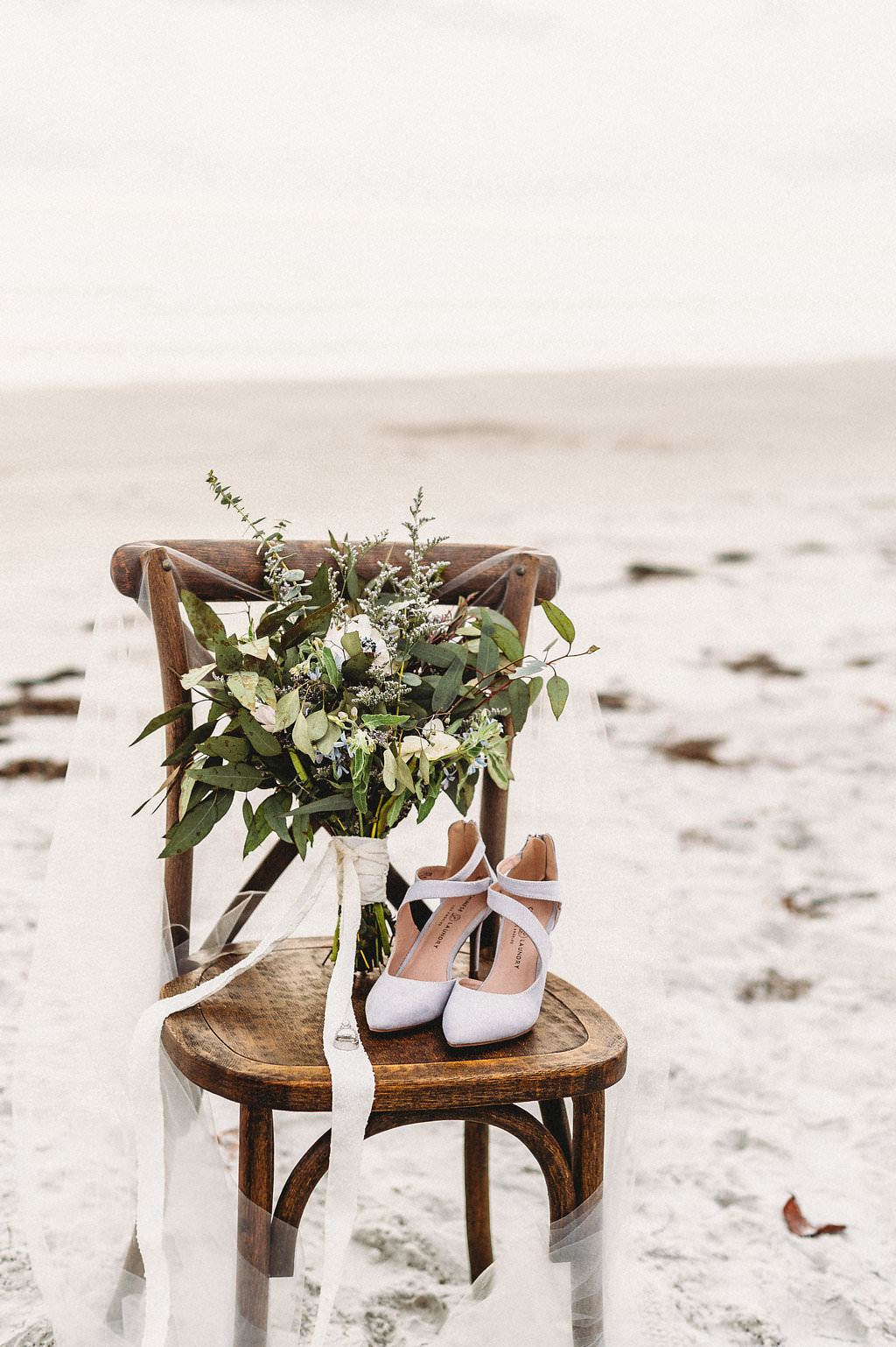 Wooden Ceremony Chairs with Greenery and White Flower Bouquet, White Pointed Shoes, Wedding Rings and Veil on Sandy White St. Pete Beach Wedding