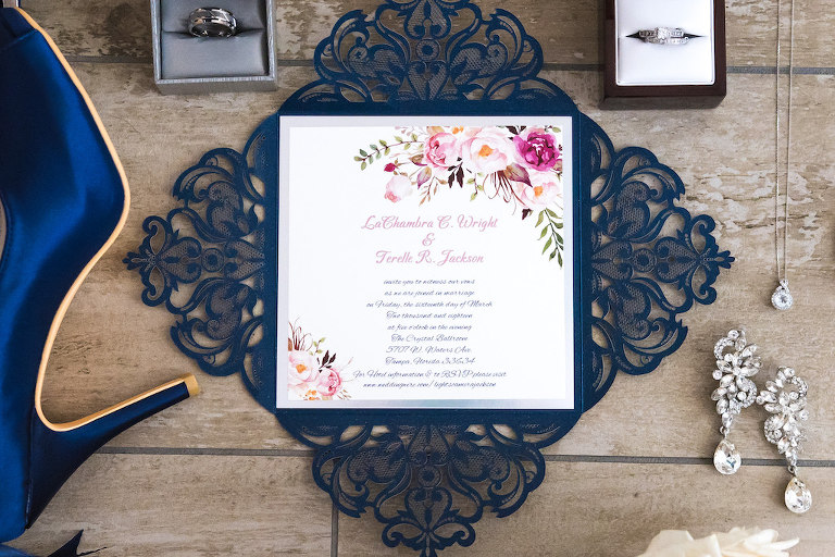 Romantic Navy Blue Lasercut Design and White and Pink Floral Square Wedding Invitation, Diamond Chandelier Earrings, Diamond Necklace, Wedding Bands in Ringboxes and Blue Sating Peep Toe Shoes