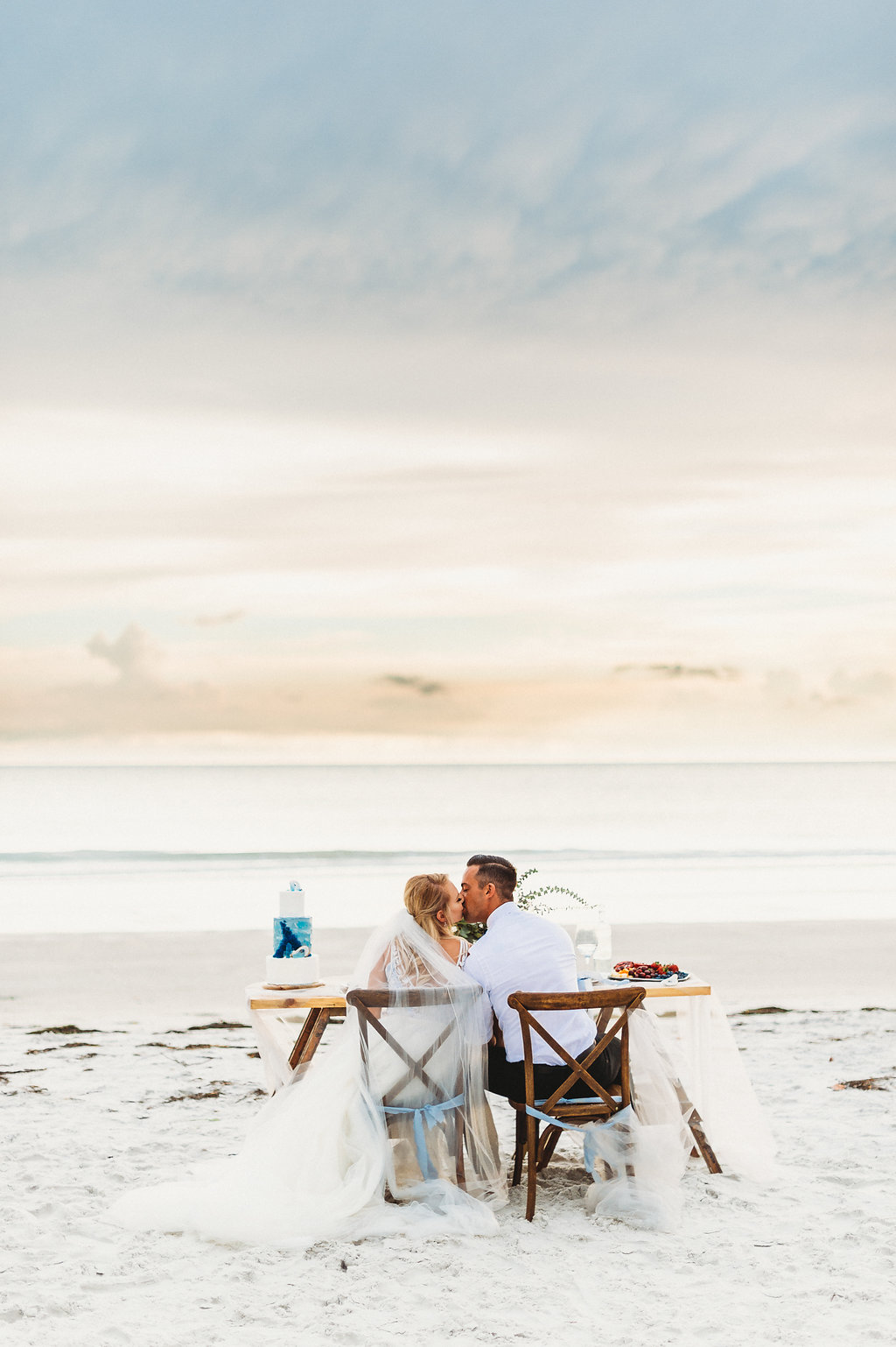 Waterfront, Sandy White Redington Beach Wedding Reception Bride and Groom Portrait in Wooden Crossback Chairs with Tulle