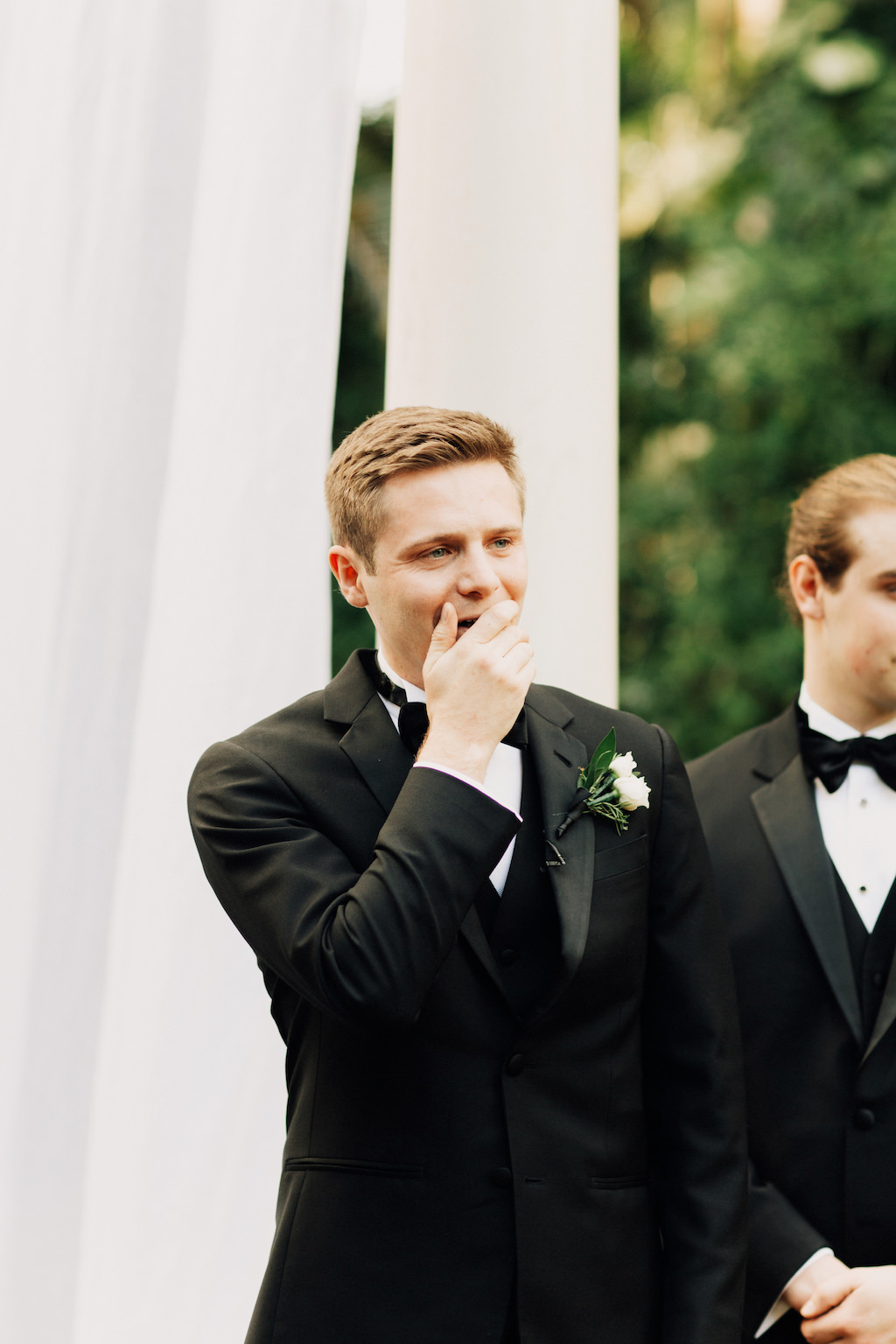 Groom's Reaction to Watching Bride Walk Down the Ceremony Aisle in Black Tuxedo