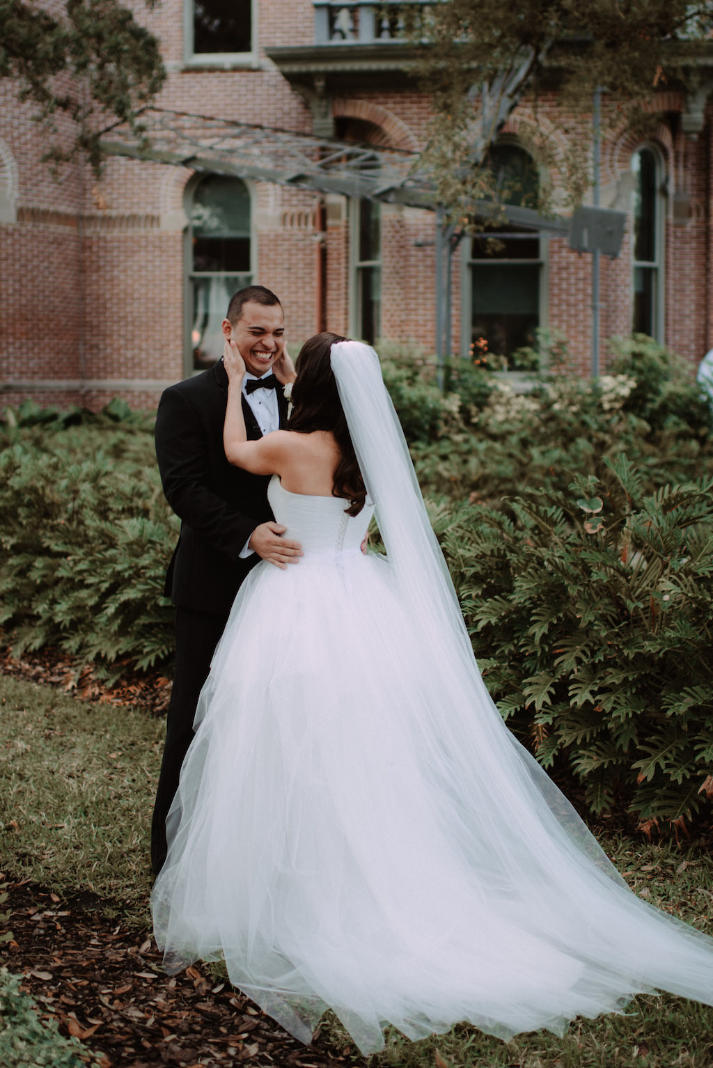 Outdoor Bride and Groom First Look Wedding Portrait, Groom in Black Tuxedo with Black Bowtie and White Rose Boutonniere, Bride in White Sweetheart Strapless Tulle Wedding Dress and Tulle Cathedral Length Veil | The University of Tampa