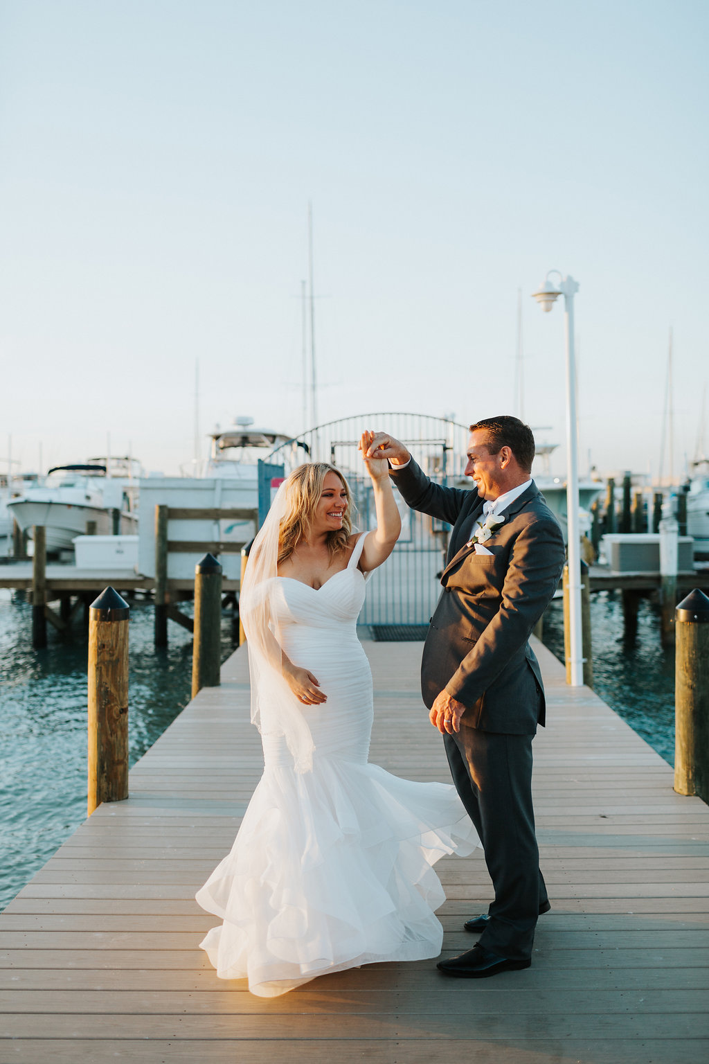 Romantic, Waterfront Bride and Groom Wedding Portrait, Bride in Mikaella Off the Shoulder, Sweetheart Wedding Dress and Tulle Veil, Groom in Grey Suit and White Cala Lillie Boutonniere   St. Pete Beach Wedding Venue Isla Del Sol Yacht and Country Club
