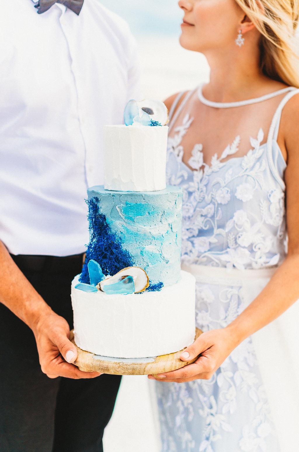 Coastal, Redington Shores Bride and Groom Wedding Portrait Holding Three Tier White and Blue Wedding Cake