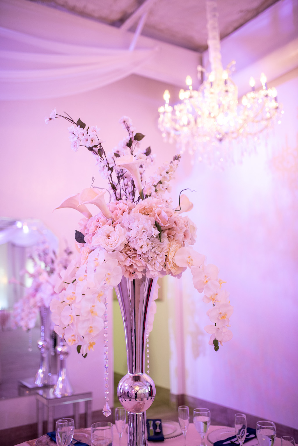 Elegant Indoor Wedding Reception Decor Tall Silver Vase With White Orchids Cala Lillies And Hanging Crystals Centerpiece And Pink Uplighting Marry Me Tampa Bay Local Real Wedding Inspiration Vendor