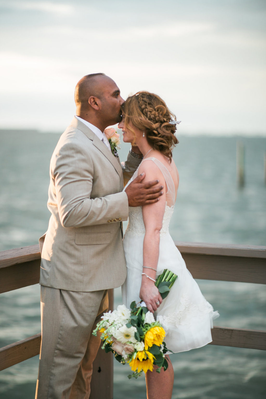 Intimate, Outdoor Waterfront Bride and Groom Wedding Portrait on Dock, Bride wearing White Tank Top Strap Short Reception Wedding Dress with Yellow Sunflower, White Daisy and Greenery Floral Bouquet and Braid, Groom in Tan Suit and Blush Pink Rose Boutonniere | Dunedin Wedding Venue Beso Del Sol Resort