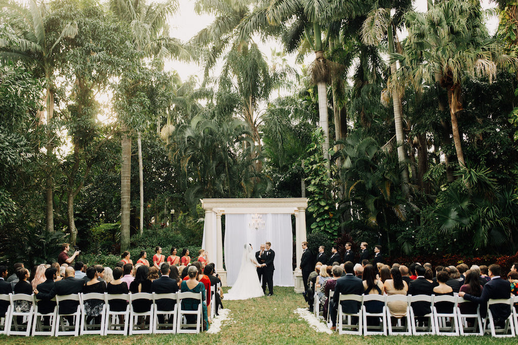 Elegant Outdoor Ceremony Wedding Portrait, Draped Ivory Ceremony Pillar Arch with White Drapery and Crystal Chandelier   St. Pete Wedding Venue The Sunken Gardens
