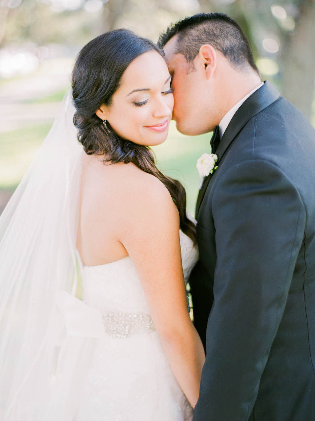 Bride and Groom Wedding Portrait, Groom in Black Tuxedo and White Floral Boutonniere, Bride in Lace Strapless Wedding Dress with Rhinestone Belt and Veil | Tampa Bay Wedding Hair Michele Renee The Studio | St. Petersburg Makeup LDM Beauty Group | Lindsay Does Makeup