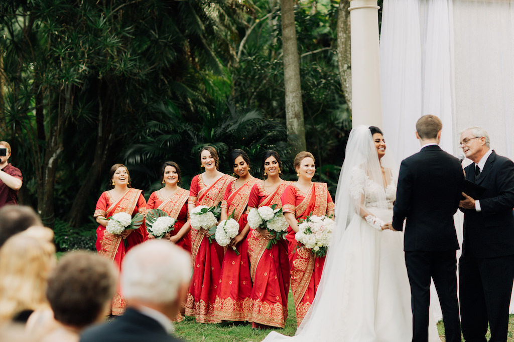Indian Fusion Wedding Outdoor Garden Wedding Ceremony, Bridesmaids in Red and Gold Sarees with White Floral Bouquets, Groom in Black Tuxedo, Bride in Long Sleeve Illusion and Lace A-Line Wedding Dress and Veil   St. Petersburg Wedding Venue The Sunken Gardens