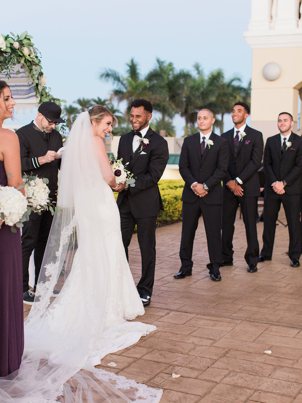 Outdoor Wedding Ceremony Portrait, Bride in Illusion Spaghetti Strap Illusion Lowback Lace Dress and Cathedral Long Veil, Groom in Black Tuxedo and Red and White Flower Boutonniere, Groomsmen in Black Tuxedos and Deep Purple Ties with White Flower Boutonniere, Greenery and White Rose Arch   Clearwater Beach Wedding Venue Feather Sound Country Club