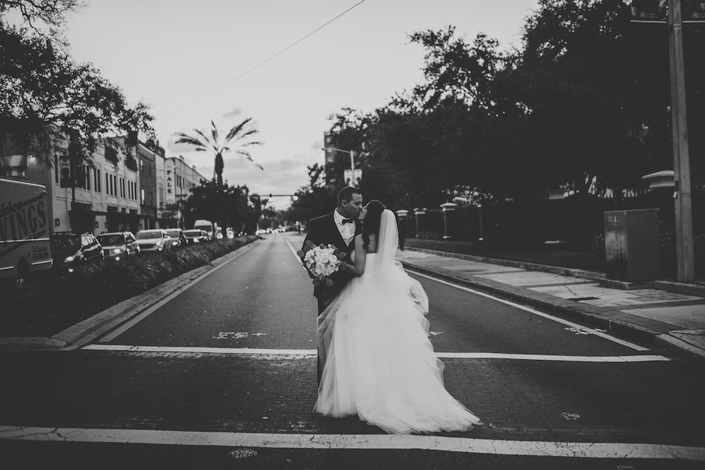 Black and White Outdoor Bride and Groom South Tampa Wedding Portrait, Groom in Black Tuxedo with Black Bowtie, Bride in White Sweetheart Strapless Tulle Wedding Dress and Tulle Cathedral Length Veil with Rose and Peonies Bouquet | Bridal Shop The Bride Tampa