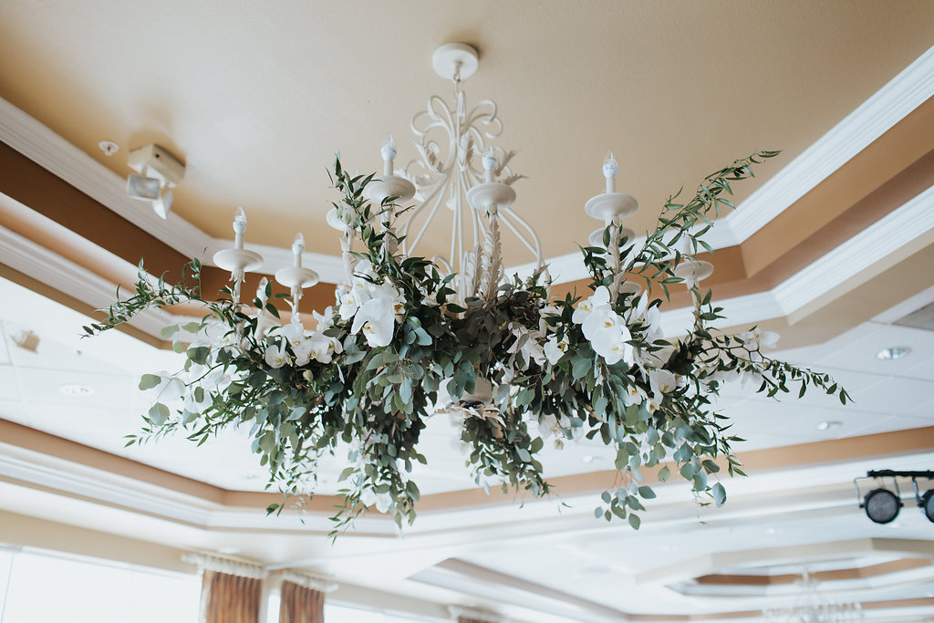 Ballroom Wedding Ceremony Décor with Greenery and White Floral Draped Chandelier   St. Pete Wedding Venue Isla Del Sol Yacht and Country Club