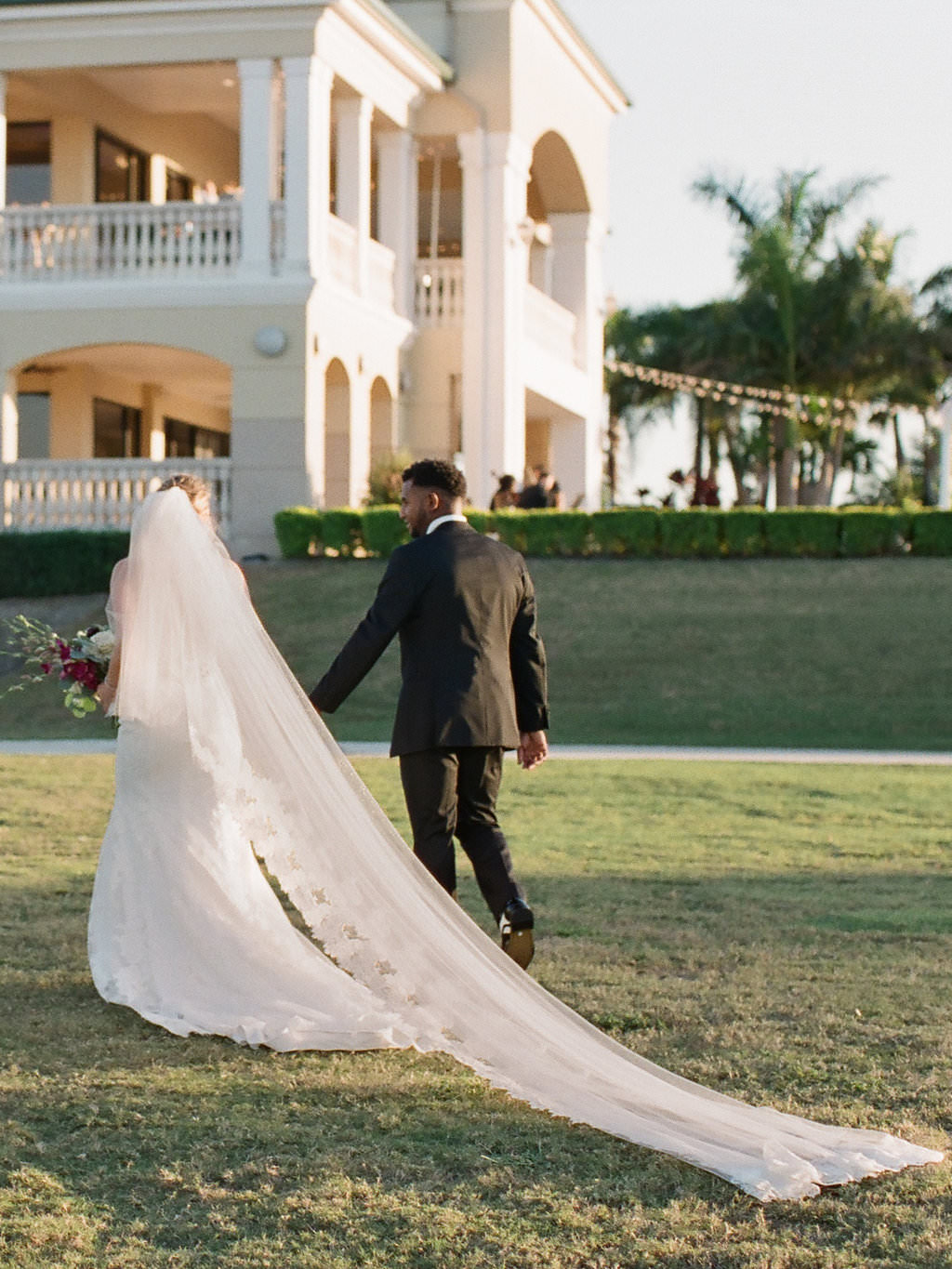 Outdoor Wedding Ceremony Exit Portrait, Bride in Illusion Spaghetti Strap Illusion Lowback Lace Dress and Cathedral Long Veil, Groom in Black Tuxedo   Clearwater Beach Wedding Venue Feather Sound Country Club