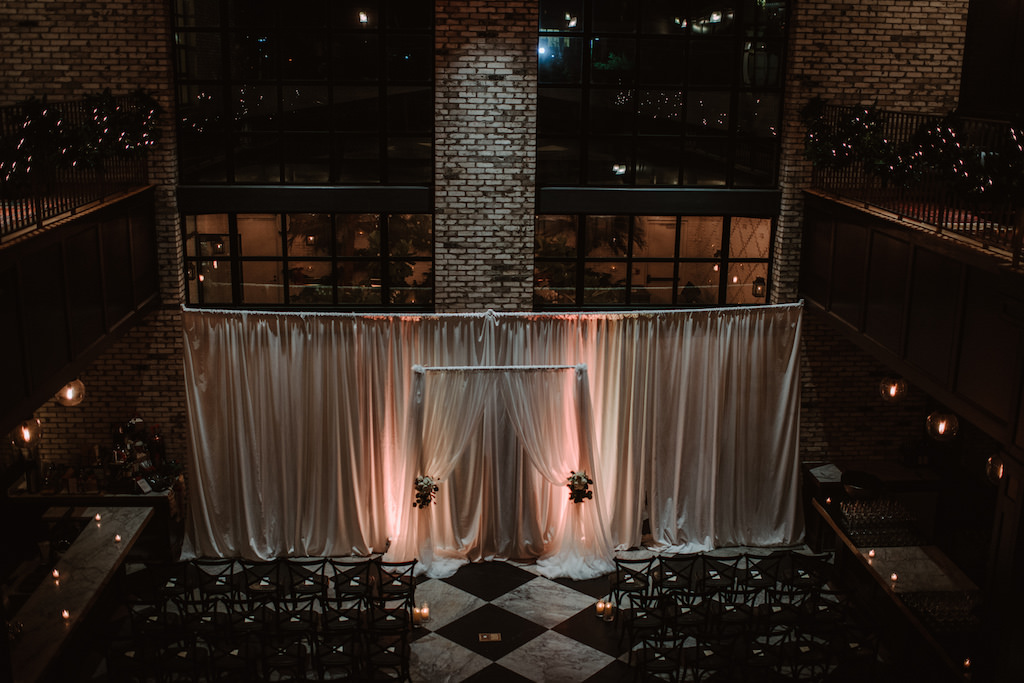 Indoor Wedding Ceremony Arch Decor with White Draping, Blush Pink Uplighting and White with Greenery Florals | South Tampa Historic Wedding Venue The Oxford Exchange