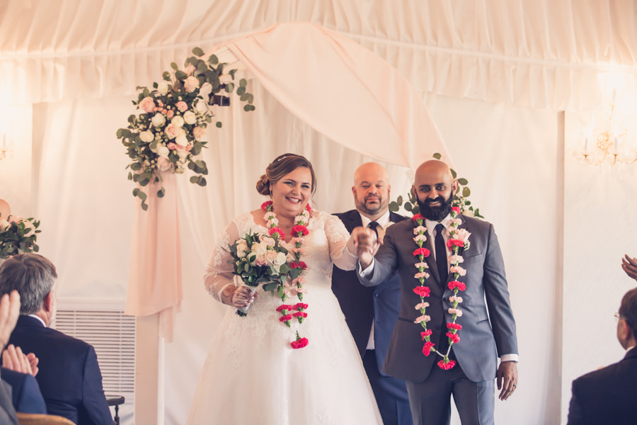 Bride and Groom Wedding Ceremony Portrait Wearing Pink Floral Leis, White and Blush Drapery Background with Pink, White and Greenery Floral Bouquet   Tampa Bay Wedding Photographer Luxe Light Photography   Tampa Bay Wedding Venue Safety Harbor Resort and Spa