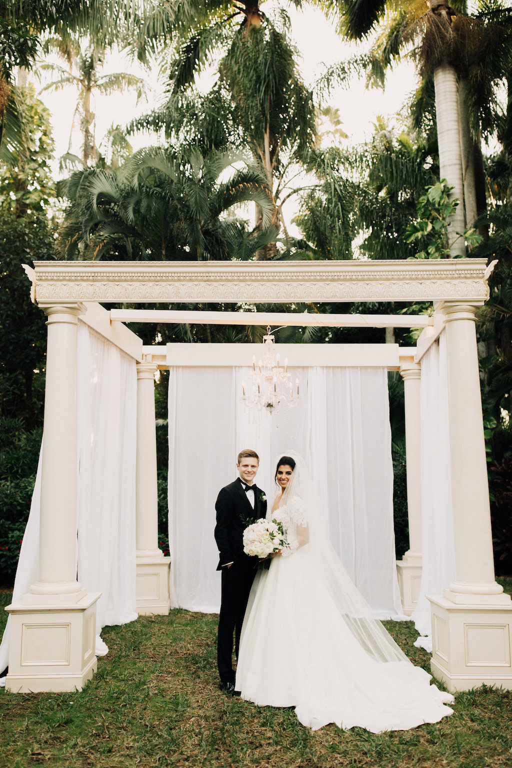 Elegant Outdoor Bride and Groom Wedding Portrait, Ivory Ceremony Pillar Arch with White Drapery and Crystal Chandelier   St. Pete Wedding Venue The Sunken Gardens