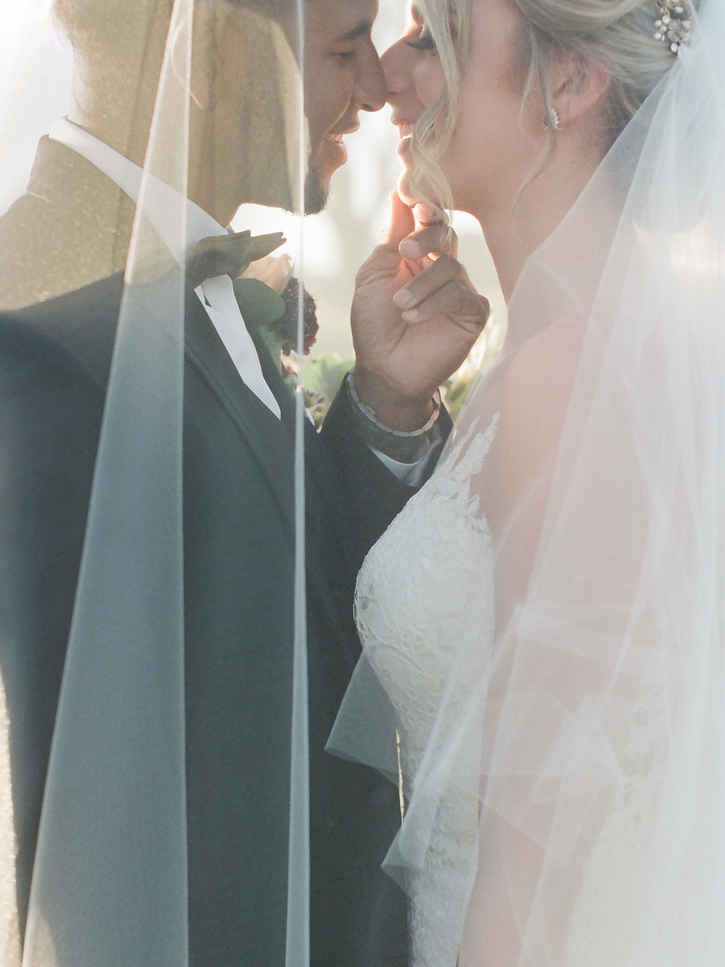 Creative Outdoor Wedding Portrait Under Veil, Bride in Spaghetti Strap Illusion Lowback Lace Dress with Buttons, Curled Hair Updo with Floral Headpiece, Groom in Black Tuxedo, Black Bowtie, White and Red Flower Boutonniere   Tampa Wedding Hair and Makeup Artist LDM Beauty Group