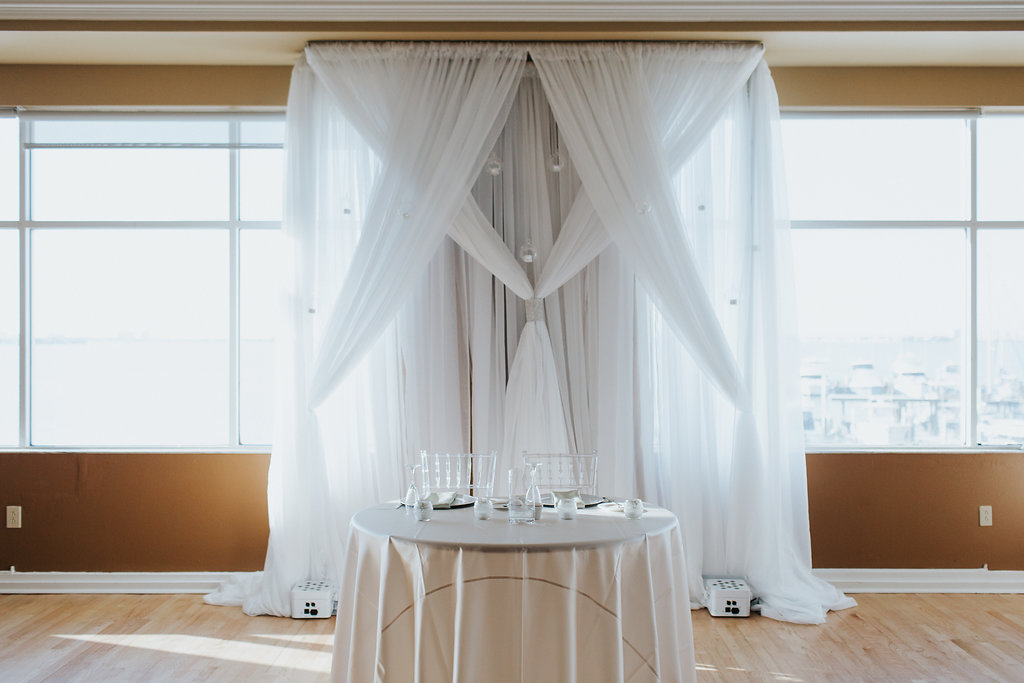 Indoor Ballroom Wedding Reception Sweetheart Table with White Linen and Decorative Silver Hanging Balls Backdrop, White Acrylic Chiavari Chairs, Off-White Tablecloth   St. Pete Wedding Venue Isla Del Sol Yacht and Country Club   Wedding Rentals Over the Top Linen Rentals and Gabro Event Rentals