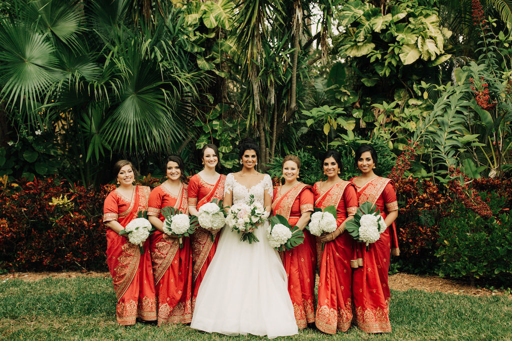 Indian Fusion Outdoor Garden Bridal Party Portrait, Bridesmaids in Red and Gold Sarees with White Hydrangeas Bouquets, Bride in Long Sleeve Illusion and Lace A-Line Wedding Dress with Blush Pink and White Floral Bouquet | St. Petersburg Wedding Venue The Sunken Gardens