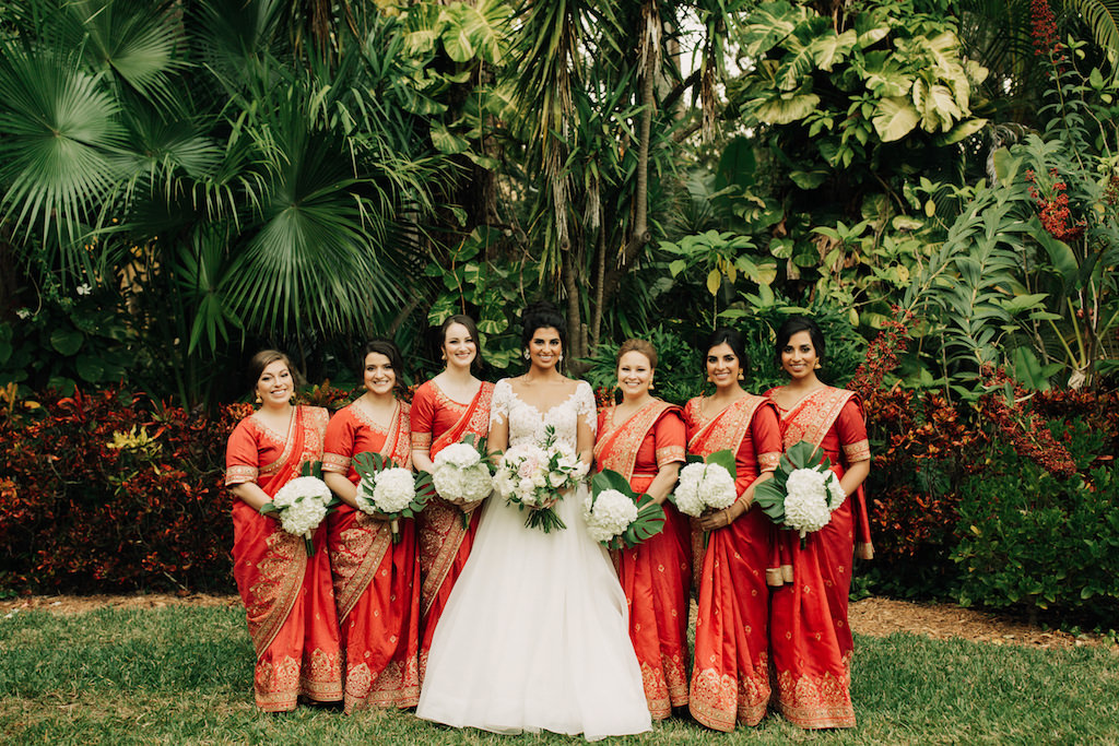 Indian Fusion Outdoor Garden Bridal Party Portrait, Bridesmaids in Red and Gold Sarees with White Hydrangeas Bouquets, Bride in Long Sleeve Illusion and Lace A-Line Wedding Dress with Blush Pink and White Floral Bouquet   St. Petersburg Wedding Venue The Sunken Gardens