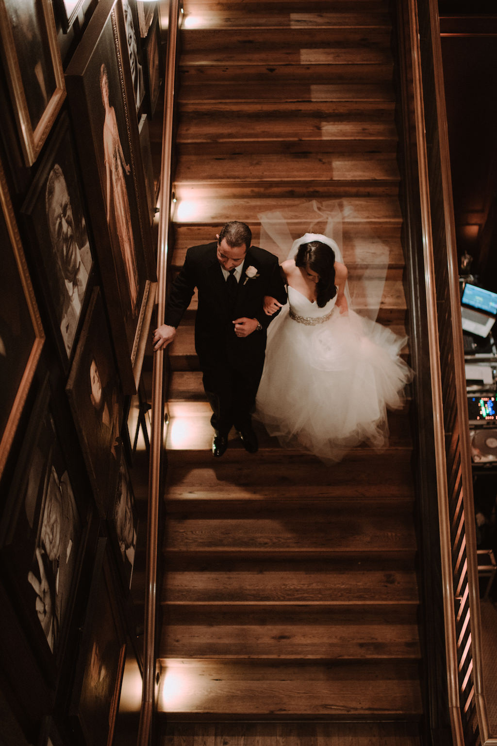 Indoor Wedding Portrait on Staircase, Bride in Sweetheart Strapless Tulle Wedding Dress with Rhinestone Belt and Cathedral Length Tulle Veil, Groom in Black Tuxedo with Black Bowtie and White Rose Boutonniere | South Tampa Historic Wedding Venue The Oxford Exchange | Bridal Shop The Bride Tampa