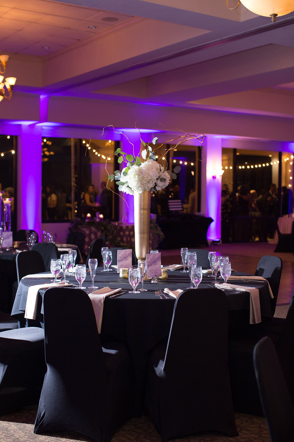 Indoor Ballroom Venue Decor, Round Reception Tables with Tall Gold Vase and White Hydrangeas, Silver Dollar Eucalyptus Centerpieces, Black Tablecloth and White Linen Napkins and Black Linen Covered Chairs   Clearwater Wedding Venue Feather Sound Country Club