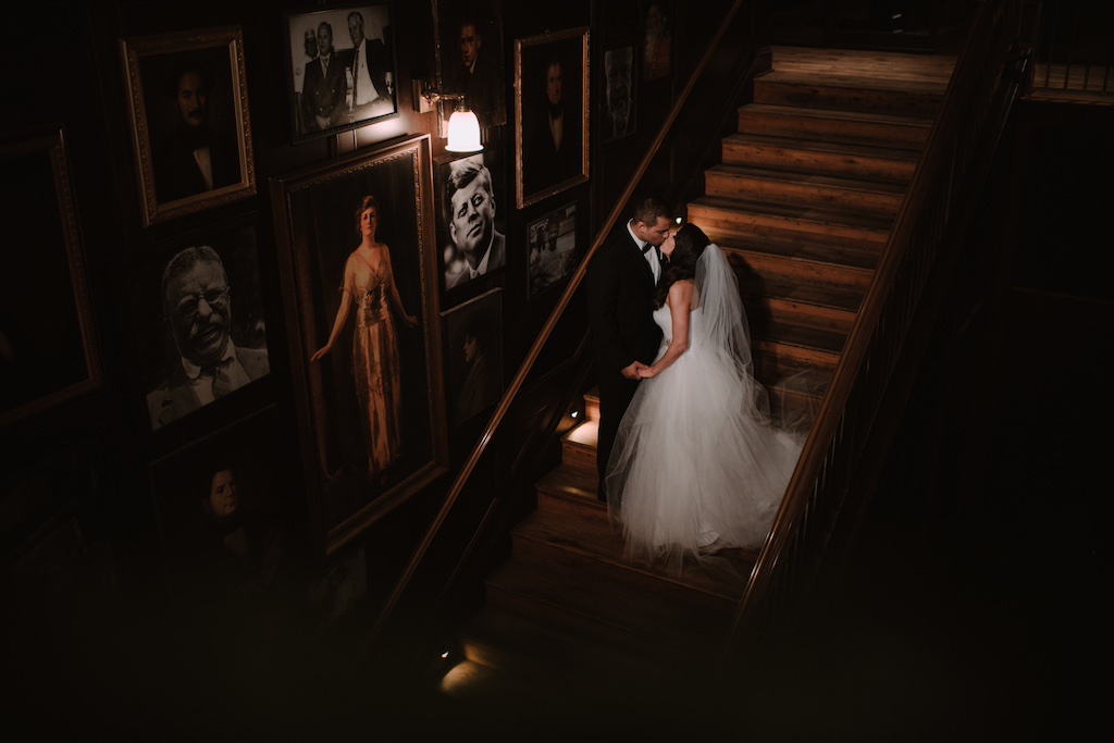 Indoor Wedding Portrait on Staircase, Bride in Sweetheart Strapless Tulle Wedding Dress with Rhinestone Belt and Cathedral Length Tulle Veil, Groom in Black Tuxedo with Black Bowtie and White Rose Boutonniere | Tampa Historic Wedding Venue The Oxford Exchange | Bridal Shop The Bride Tampa