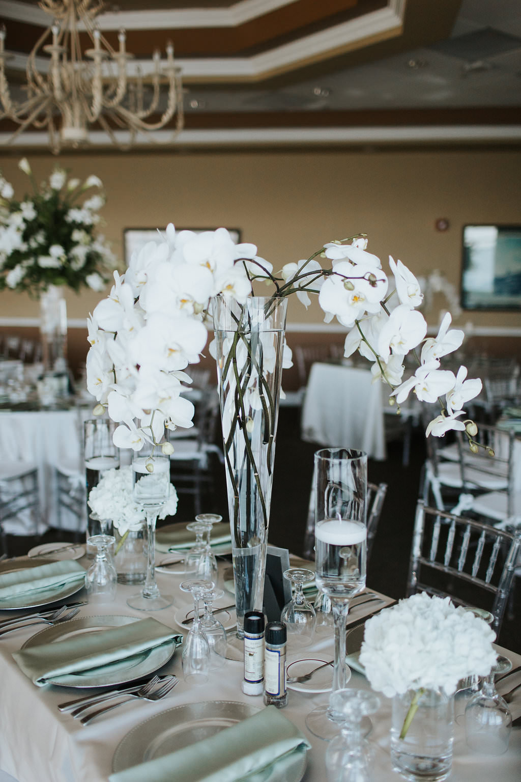 Elegant, Ballroom Wedding Reception Decor, Tall White Orchid Centerpiece in Glass Cylinder on White Satin Tablecloth, with Silver Plate Chargers and Mint Green Linens   St. Petersburg Wedding Venue Isla Del Sol Yacht and Country Club   St. Petersburg Wedding Rentals Over the Top Rentals and Gabro Event Rentals